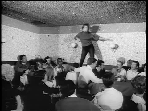 b/w 1965 woman in black tights dancing on table in nightclub as crowd claps / newsreel - tights stock videos & royalty-free footage