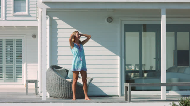 A woman in blue dress spinning around outside home