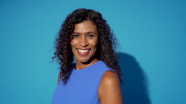 a woman in blue smiles and laughs - studio shot stock videos & royalty-free footage