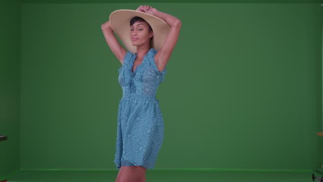 vidéos et rushes de woman in blue sun dress and sunhat enjoying on green screen - robe d'été