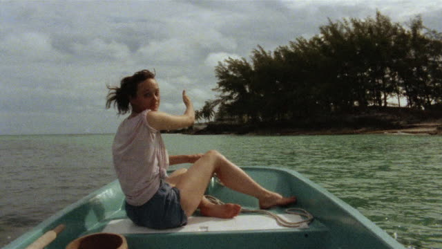 MS Woman in boat pointing out to sea and shore of island / North Bimini, Bahamas