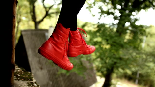 Woman in bright red leather ankle boots
