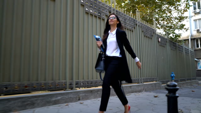 Woman in business suit walking on the street.