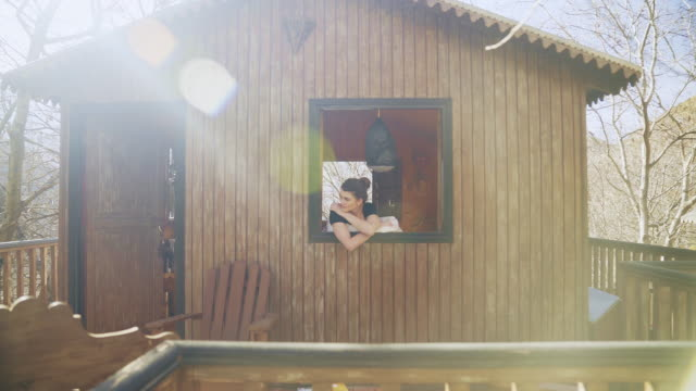 woman in cabin's window. looking at mountain view - hut stock videos & royalty-free footage