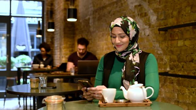 frau in café mit handy und blickte zu gesicht kamera - islam stock-videos und b-roll-filmmaterial
