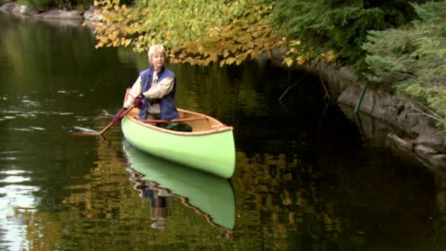 zo ha ws woman in canoe on smoke lake, algonquin provincial park, ontario, canada - ruderboot stock-videos und b-roll-filmmaterial