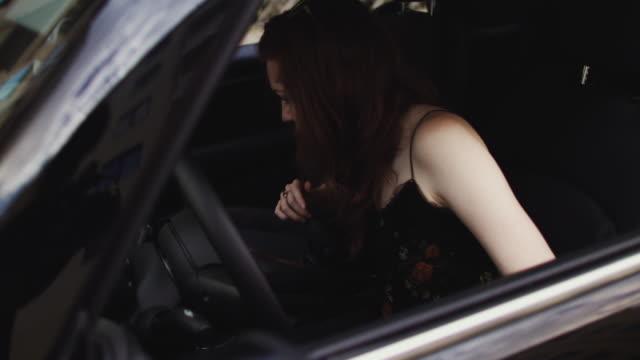 Woman in car getting accustomed to carsharing car