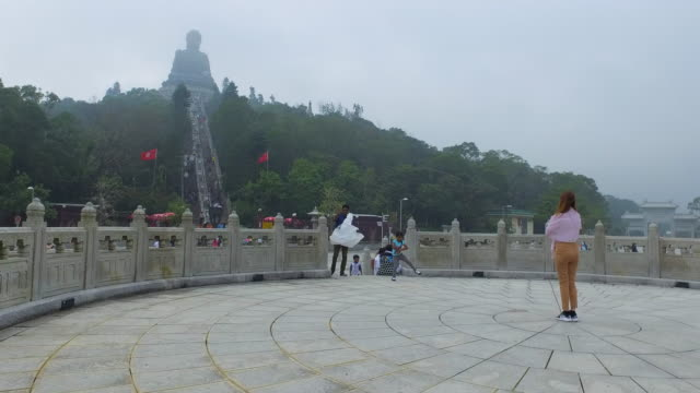woman in centre of circular paved area with tian tan buddha statue in background - hong kong, china - tian tan buddha stock videos and b-roll footage