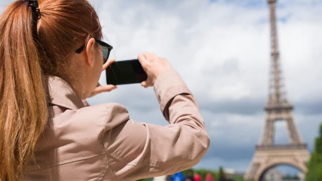 Woman in Champ de Mars garden taking pictures of Eiffel Tower