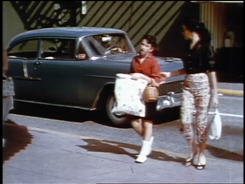 1957 woman in clamdigger pants + girl walking in parking lots with shopping bags / feature - 1957 stock videos & royalty-free footage