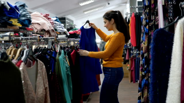 woman in clothes store - clothes rail stock videos & royalty-free footage