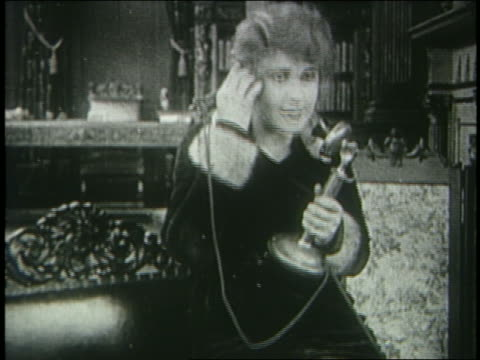 stockvideo's en b-roll-footage met b/w 1915 woman (pearl white) in coat talking on telephone + smiling / silent serial - 1915