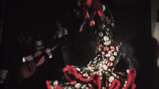 A woman in colorful traditional dress dances a wild flamenco in Madrid, Spain