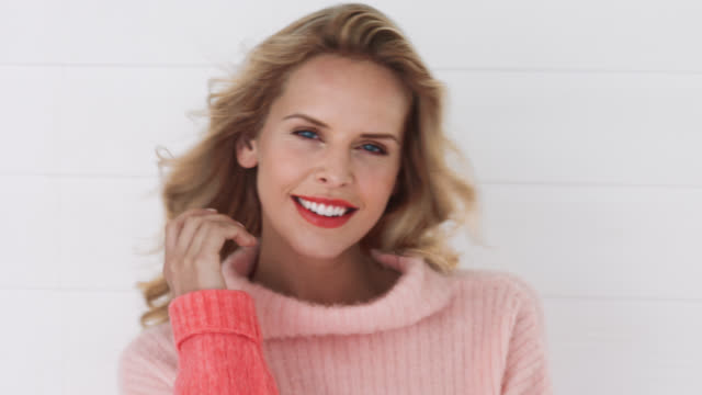 a woman in coral jumper smiling to camera with breeze blowing hair - rufsig bildbanksvideor och videomaterial från bakom kulisserna