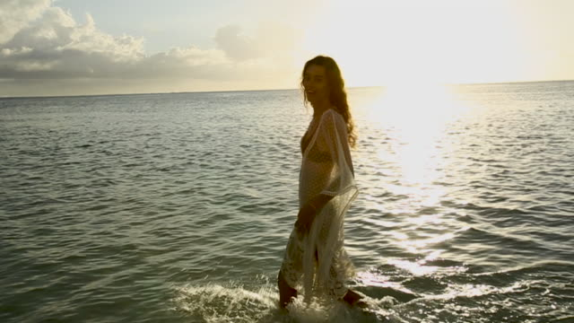 vidéos et rushes de woman in crochet tunic wades in shallow water at sunset, handheld - maillot de bain