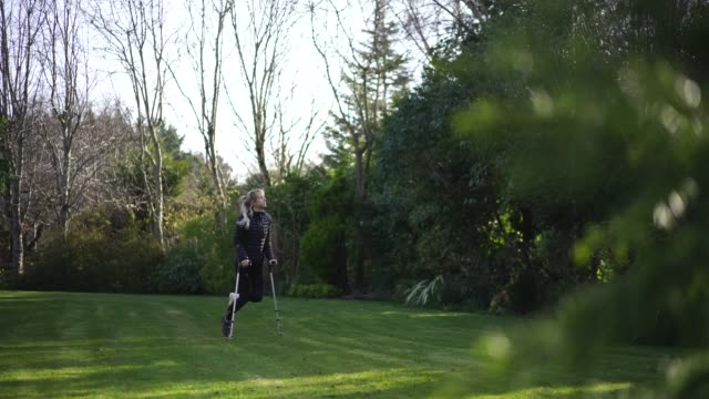 woman in crutches with cast walks through garden - crutch stock videos & royalty-free footage