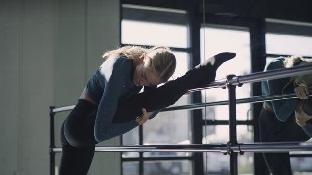 stockvideo's en b-roll-footage met woman in dance studio stretching leg on ballet barre near mirror  / lehi, utah, united states - lehi