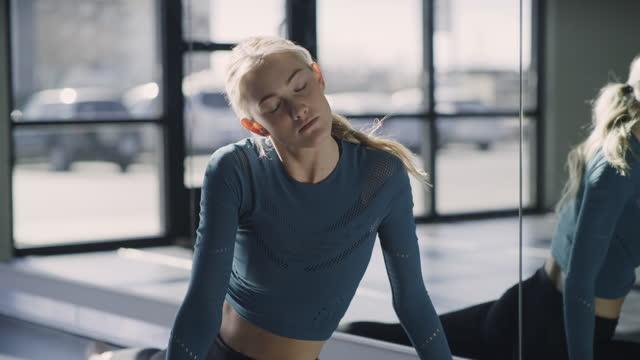 stockvideo's en b-roll-footage met woman in dance studio stretching neck and legs near mirror  / lehi, utah, united states - lehi
