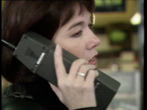 Woman in dark jacket talks on large mobile phone turns toward and away from camera; 1980s