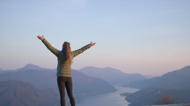 woman in down jacket stands in freedom pose looking out at view - gratitude stock videos & royalty-free footage