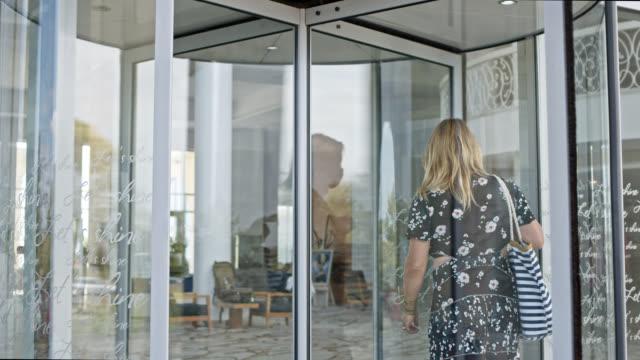 vidéos et rushes de woman in dress and with shoulder bag enters hotel business building - porte entrée
