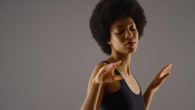 vídeos de stock e filmes b-roll de  woman in dress dancing slowly - studio shot