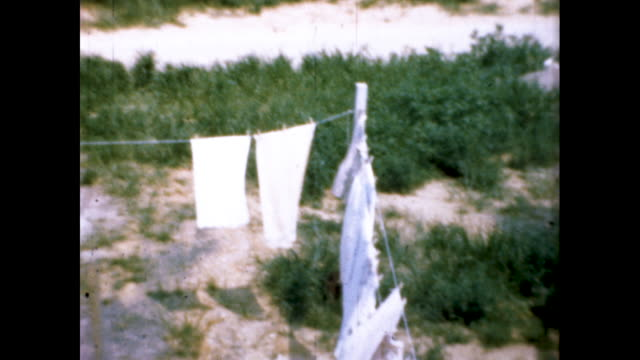 woman in dress hanging clothes on a clothesline and looking up at the camera and smiling; mostly white clothes and mostly pants on another clothesline - housework stock videos & royalty-free footage