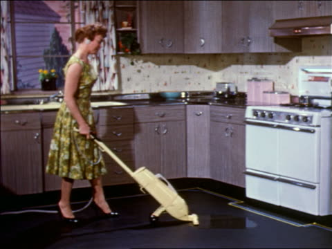 1959 woman in dress + high heels using floor polisher on kitchen floor / industrial