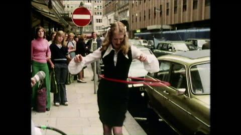 woman in dress hula hoops on city street; 1974 - hüfte stock-videos und b-roll-filmmaterial