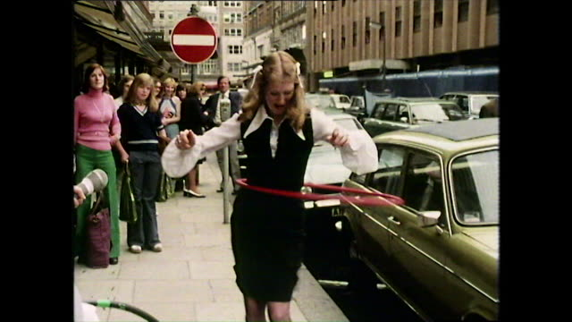 woman in dress hula hoops on city street; 1974 - torso stock videos & royalty-free footage