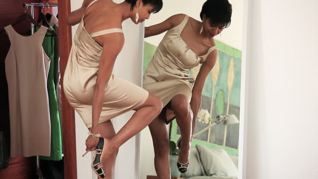 woman in dress putting on high heels and applying lipstick in mirror - scarpe video stock e b–roll