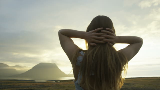 woman in dress running fingers through hair while watching the sunset