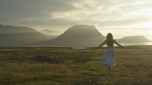 woman in dress running through field in iceland - 幻想点の映像素材/bロール