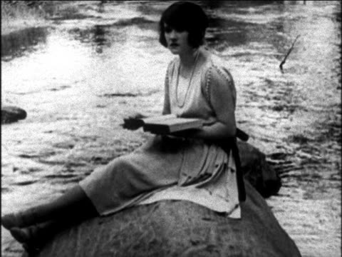 b/w 1925 woman in dress sitting on rock reading book / newsreel - 1925 stock videos & royalty-free footage