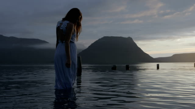 vídeos de stock, filmes e b-roll de woman in dress standing in calm ocean at sunset - vadear