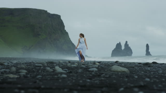 vídeos de stock, filmes e b-roll de woman in dress walking down black sand beach in iceland - coluna de calcário marítimo