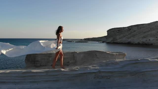 Woman in Dress Walking on Rock