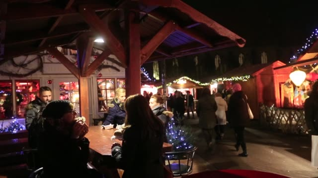 a woman in earmuffs and reindeer antlers eats wurst at a christmas market in berlin on wednesday december 10 gvs of people at the market wurst and... - 枝角点の映像素材/bロール