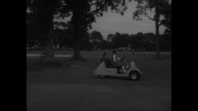 "woman in electric golf cart comes to stop next to golf course; she steps out wearing ""plus fours"" / model sitting on veranda railing with water... - golf cart stock videos & royalty-free footage"