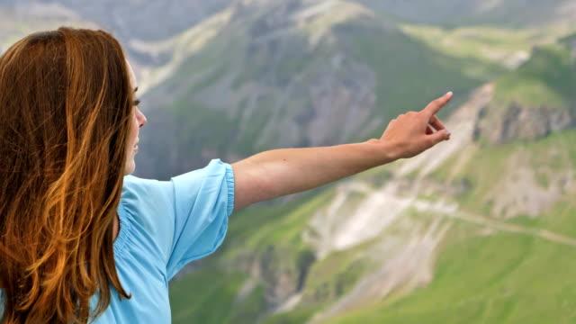 vídeos de stock, filmes e b-roll de mulher em um vestido elegante, apontando a direção nas montanhas - apontando sinal manual