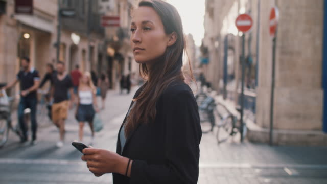 woman in european city with cell phone on summer evening - elegante kleidung stock-videos und b-roll-filmmaterial