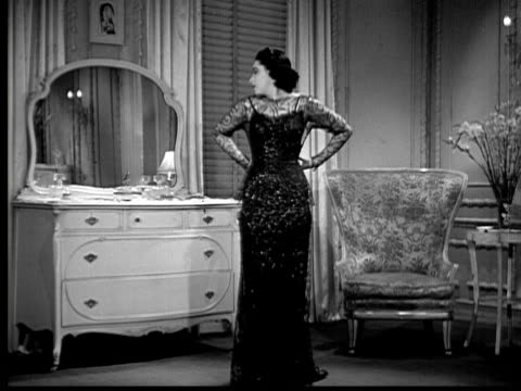 1937 B/W WS Woman (Elaine Barrie) in evening dress beginning to undress in front of mirror
