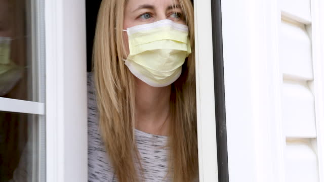 woman in face mask peeks outside door - peeking stock videos & royalty-free footage