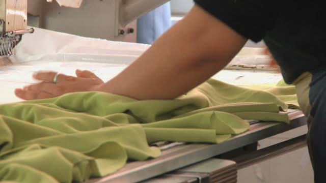 CU Woman in factory laying out clothing on embroidery machine / Ningbo, Zhejiang, China