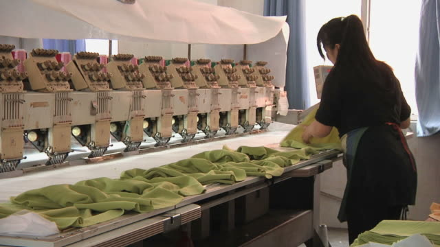 MS Woman in factory laying out clothing on embroidery machine / Ningbo, Zhejiang, China