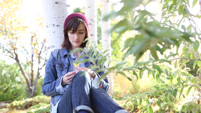 vídeos de stock, filmes e b-roll de woman in fall aspen trees writing in diary - jaqueta jeans