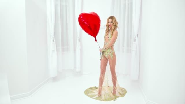 vidéos et rushes de femme en robe à la mode tenant le ballon de forme de coeur - pin up