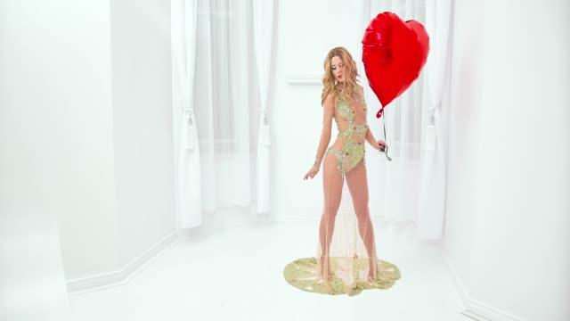vídeos de stock e filmes b-roll de woman in fashionable dress holding heart shape balloon - cintura