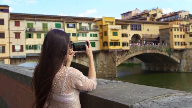 stockvideo's en b-roll-footage met vrouw in florence, die ponte vecchio fotografeert - ponte