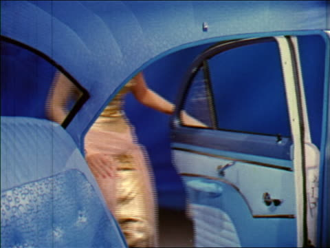 1955 woman in formalwear entering back seat of blue car in studio / industrial - evening gown stock videos and b-roll footage